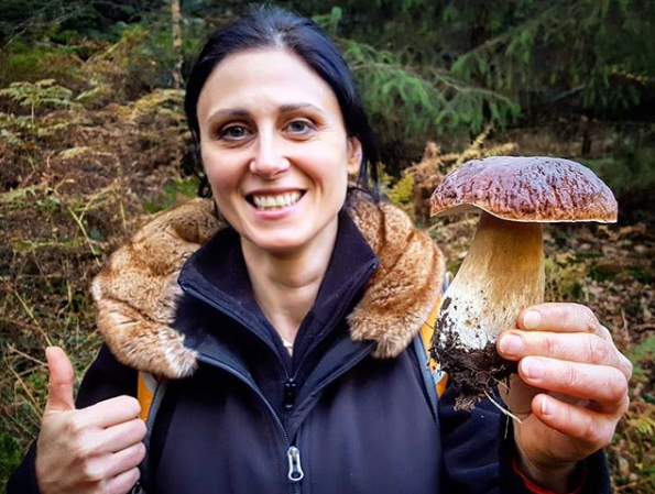 A dark-haired woman beams as she proudly holds up her first cep mushroom find in the UK with bracken and trees behind her